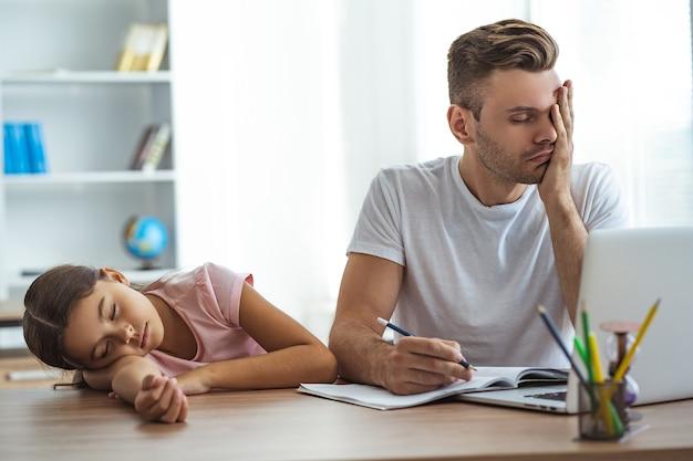 Измученный отец и дочь делают домашнее задание за столом
