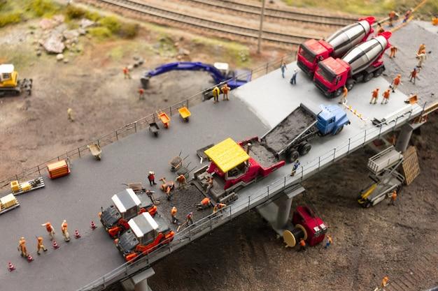 Выставка grand maket russia. рабочие и сервисные автомобили строят новый мост, фрагмент самостоятельной большой планировки в россии.