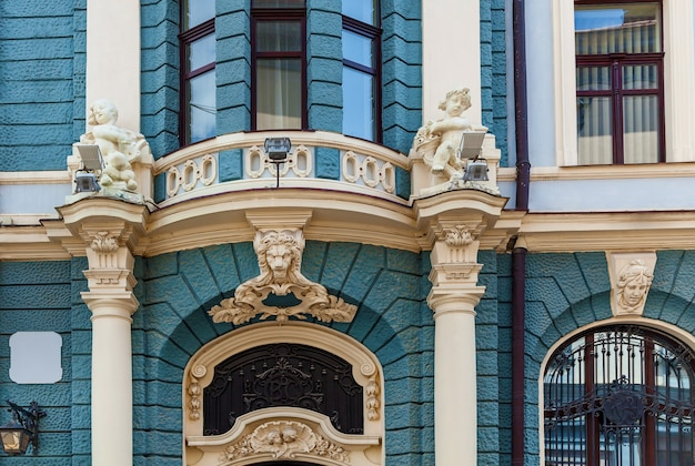 石のディテールが施された青い色のモダンでクラシックな建物の外観。