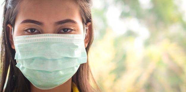 마스크를 쓴 태국 여성의 눈은 피곤하고 covid-19 바이러스에 대해 염려합니다.