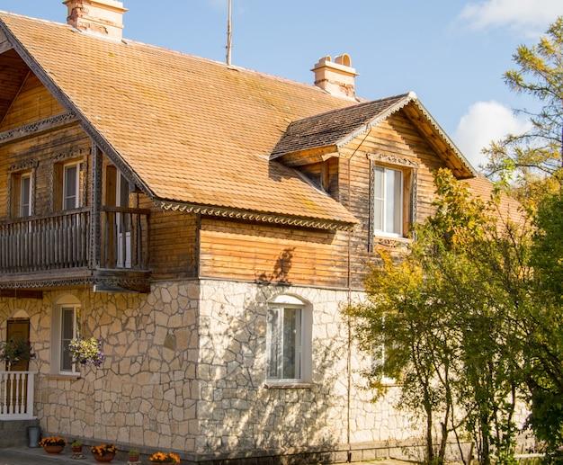 다락방과 갈색 기와 지붕이 있는 2층 석조 주택의 정면.