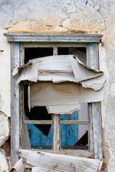窓にガラスがなく、開いた木製のドアがある、古い廃墟のレンガ造りの家のファサード