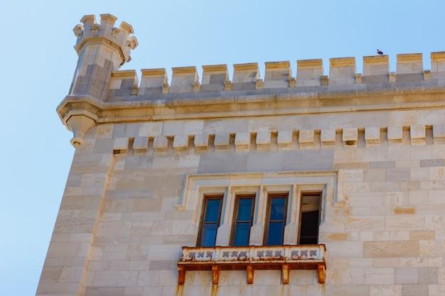 Фасад касты мирамаре на голубом небе. высокая башня замка в небе.