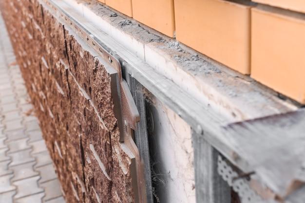 Фасад здания необходимо заменить крупным планом кирпичной стены и камня, используемого для облицовки.