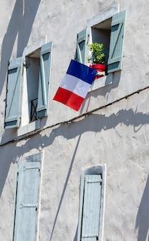 窓にフランスの国旗が描かれた建物のファサード。