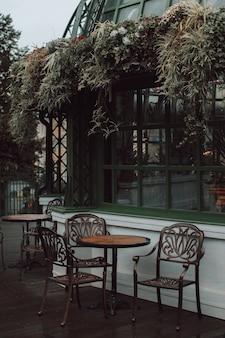 Фасад кафе украшен растениями и цветами. деревянный стол и стулья в винтажном стиле.