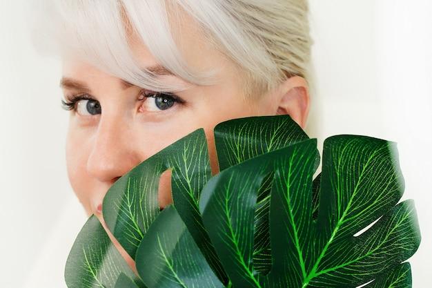 緑のモンステラの後ろに隠れた若いブロンドの女性の顔と目は、自然な共同の概念を残します...