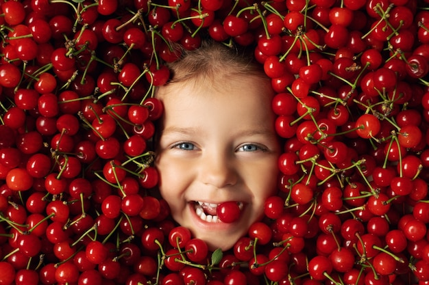 많은 수의 붉은 익은 과즙 체리에 둘러싸인 행복한 쾌활한 아이의 얼굴