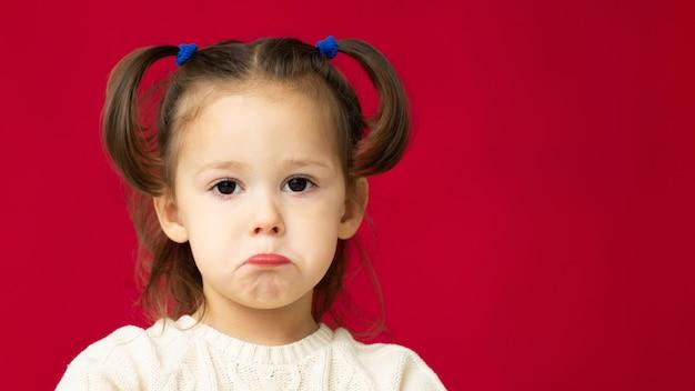 Лицо грустной маленькой симпатичной девочки 2-4 в белом вязаном платье на красном фоне. баннер