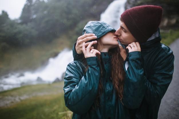 彼氏に後ろから抱かれている緑のレインコートを着た笑顔の女性の顔