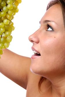Лицо молодой девушки крупным планом, гроздь спелого зеленого винограда. концепция здорового питания и молодости.