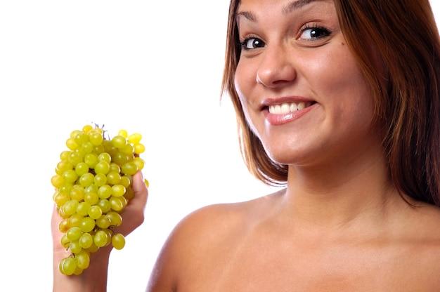 若い女の子のクローズアップの顔、熟した緑のブドウの束。健康的な食事と若さの概念。