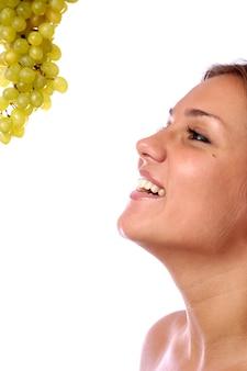 Лицо молодой девушки крупным планом, гроздь спелого зеленого винограда