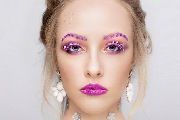 어린 소녀의 얼굴. 보라색 메이크업 모델. 멋진 눈썹 여자 초상화를 닫습니다.