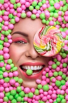 色とりどりのお菓子の中の若い女性の顔。様々なお菓子。美しい女性の笑顔
