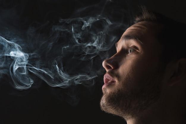 蒸気を吸う若い男の顔