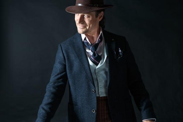 灰色の帽子を持つ若い男の肖像画の顔。杖を持ったレトロな男