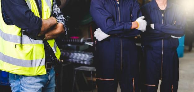 工場のエンジニアが立って腕を組んで、工場内での作業に自信を示しています。工場で働く産業職人。