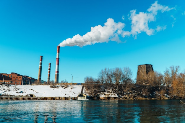 공장은 큰 파이프를 통해 오염의 흰 연기를 방출하고 있습니다