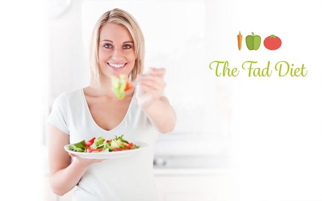 サラダを食べる格好良い女性のクローズアップに対する流行の食事療法
