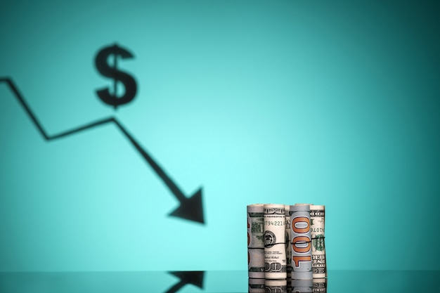 為替レートの下落。お金のロールがテーブルにあります。コピースペース