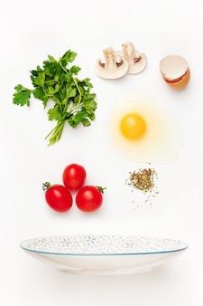 Падающие ингредиенты жареного яйца. ингредиенты для здорового завтрака.