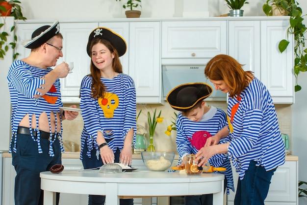 가족이 함께 요리를합니다. 부엌에있는 남편, 아내 및 자녀. 가족은 밀가루로 반죽을 반죽합니다. 부엌에서 반죽을 준비하십시오.