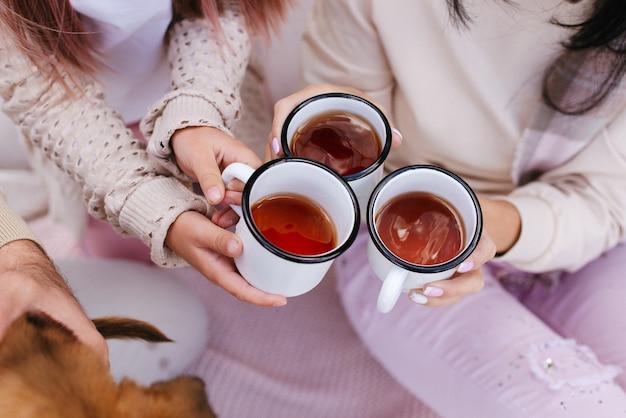 家族は鉄のマグカップからお茶を飲みます。鉄のマグカップのお茶。田舎でのピクニック。