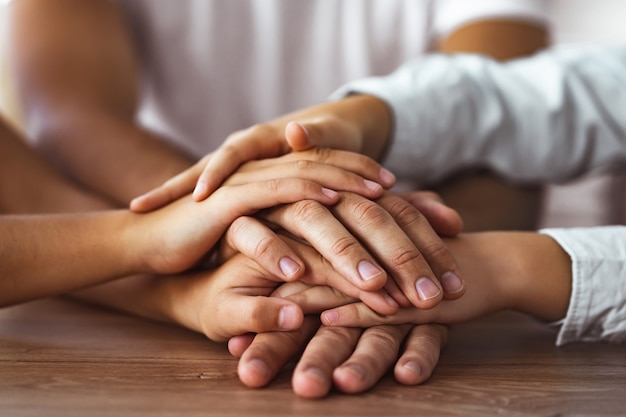 Семья держится за руки вместе за столом