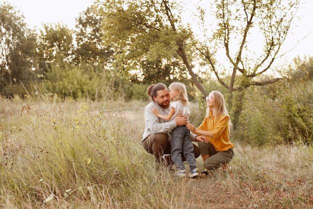 家族は散歩で自然の中で娘を抱きしめます。児童保護