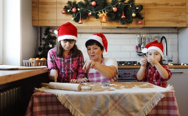 Семья готовится к новому году и готовит печенье на кухне