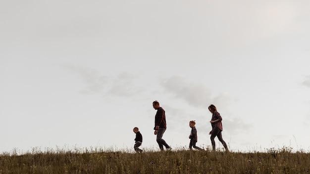 가족은 자연 속에서 쉬고 있습니다. 아빠, 엄마, 두 아들이 들판을 걷고 있습니다.