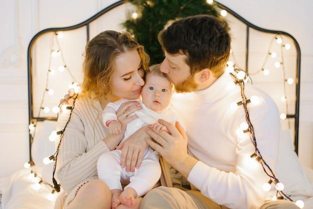가족이 침대에 앉아 있습니다. 크리스마스 장식으로 꾸며진 침실에서 엄마, 아빠, 아이가 즐거운 시간을 보내세요. 부모는 아기에게 키스