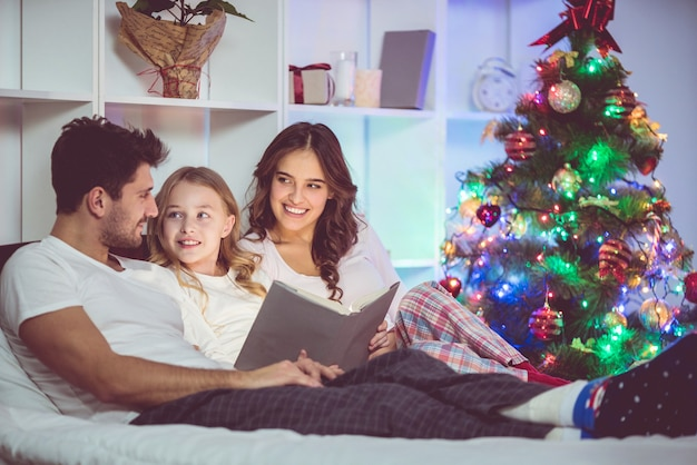 Семья лежала на кровати и читала книгу возле елки. вечернее время