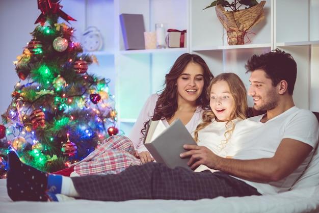 Семья лежала на кровати с книгой возле елки. вечернее время