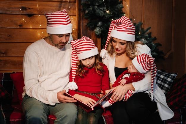 가족은 크리스마스 트리 근처의 앨범에있는 사진을 본다