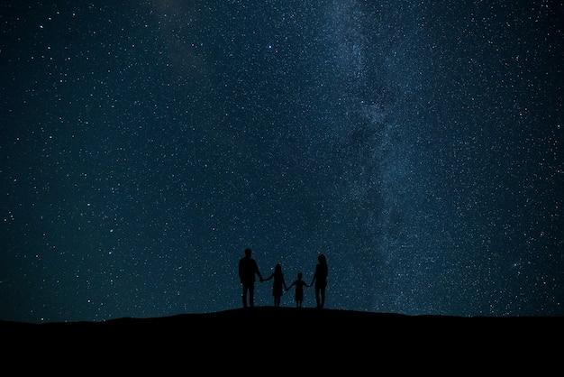 별이 있는 하늘 배경에 서 있는 가족
