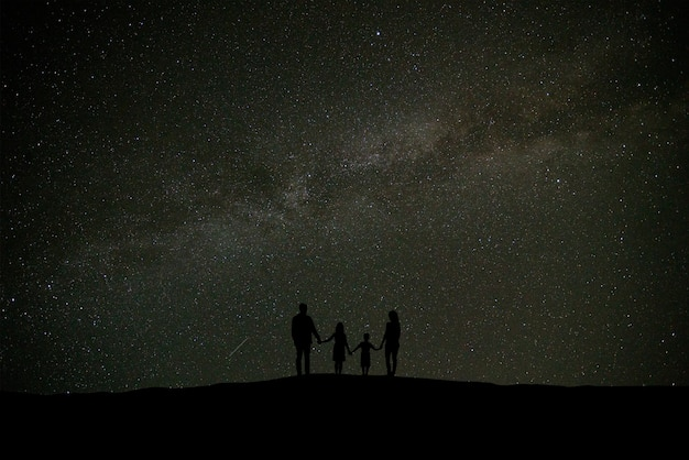 별이 빛나는 하늘을 배경으로 서 있는 가족