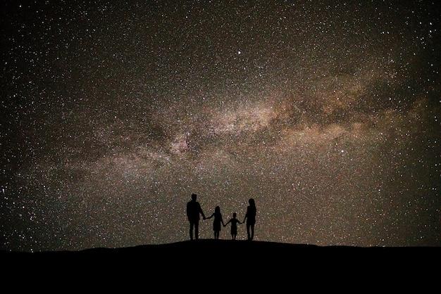 아름다운 별이 빛나는 하늘 배경에 서있는 가족
