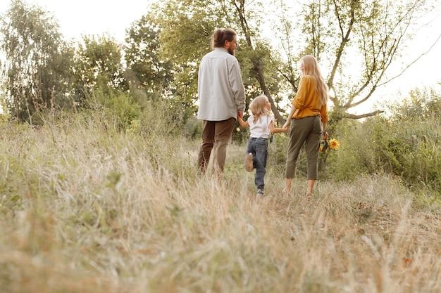 家族は自然の中を歩き、去ります。テキスト用の空き容量