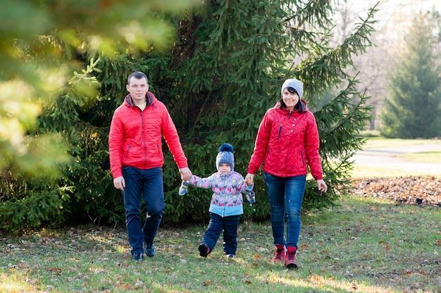 Семья гуляет по парку осенью