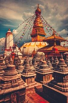 네팔 카트만두 계곡의 부다나트에 있는 유명한 불교 사리탑. 14세기에 지어졌습니다. 백그라운드에서 푸른 흐린 하늘입니다. 여행, 휴가. 빈티지 레트로 토닝 필터 오렌지 컬러