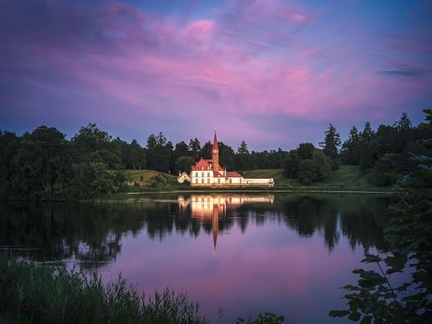 日没時に有名な修道院宮殿、日光の下でカラフルな雲。ロシア、ガッチナのおとぎ話の城。