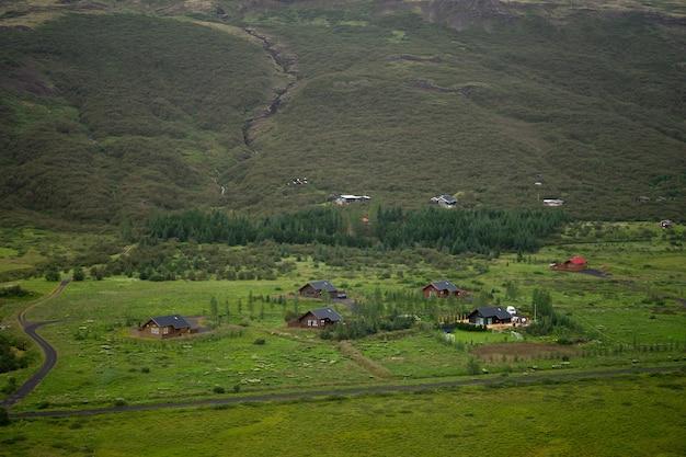 Ферма находится на холме посреди зеленого поля в сельской исландии. Premium Фотографии