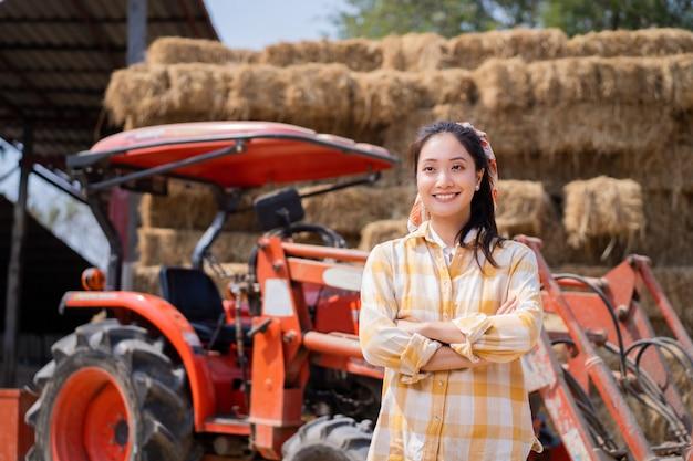 農夫、彼女はトラクターと一緒です。彼の後ろには牛に餌をやるわらの山があった