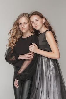 함께 그리고 회색 위에 서있는 패션 소녀