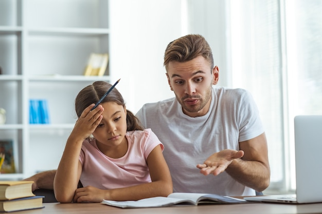 机で宿題をしている父と娘