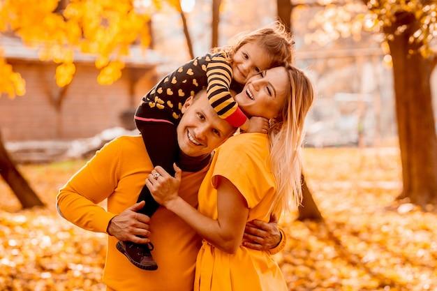 Отец и мать обнимают дочь