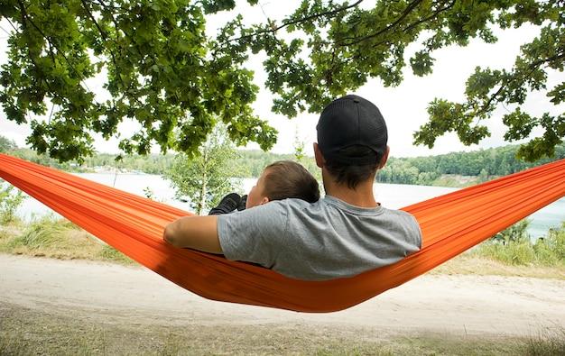 Отец и сын висят и отдыхают в гамаке в лесу.