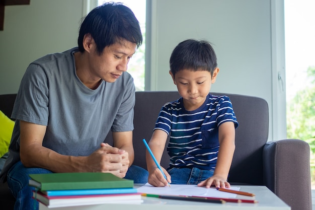 父と息子のアジアは想像力で喜んで絵を描きます。居間で宿題をしている子供たちに教える父